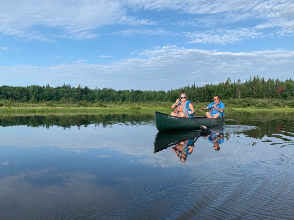 couple in a canoe on Roach Pond in Maine