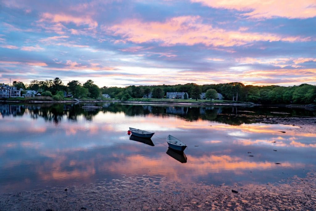 two row boats on a salt pond at sunset with purple and pink reflections in the water in Kennebunkport