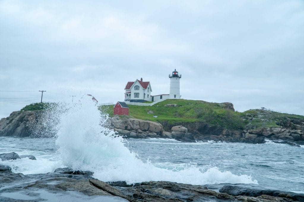 Nubble Lighthouse in Cape Neddick with a large wave splashing on the rocks in front