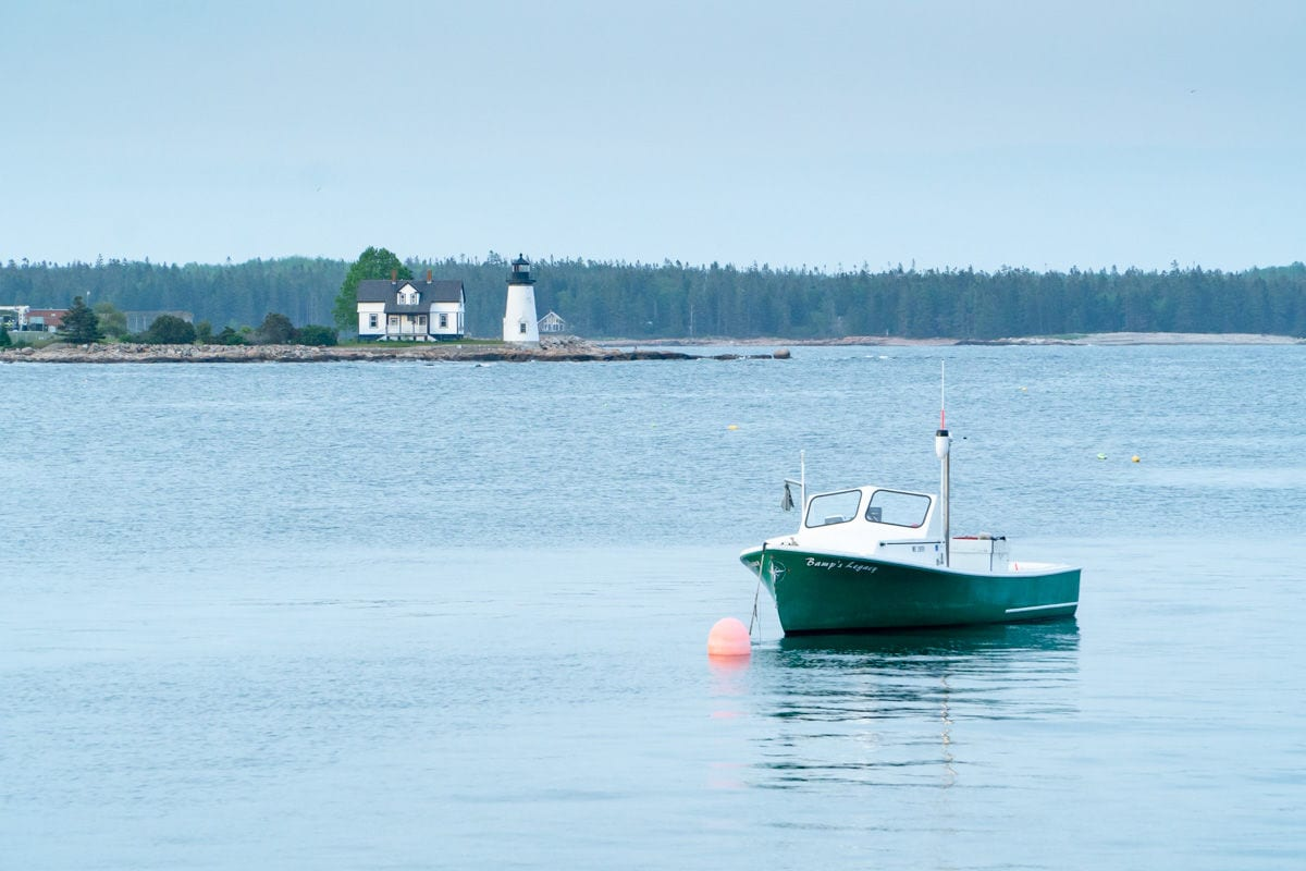 Green boat in the water in front of Prospect Harbor lighthouse