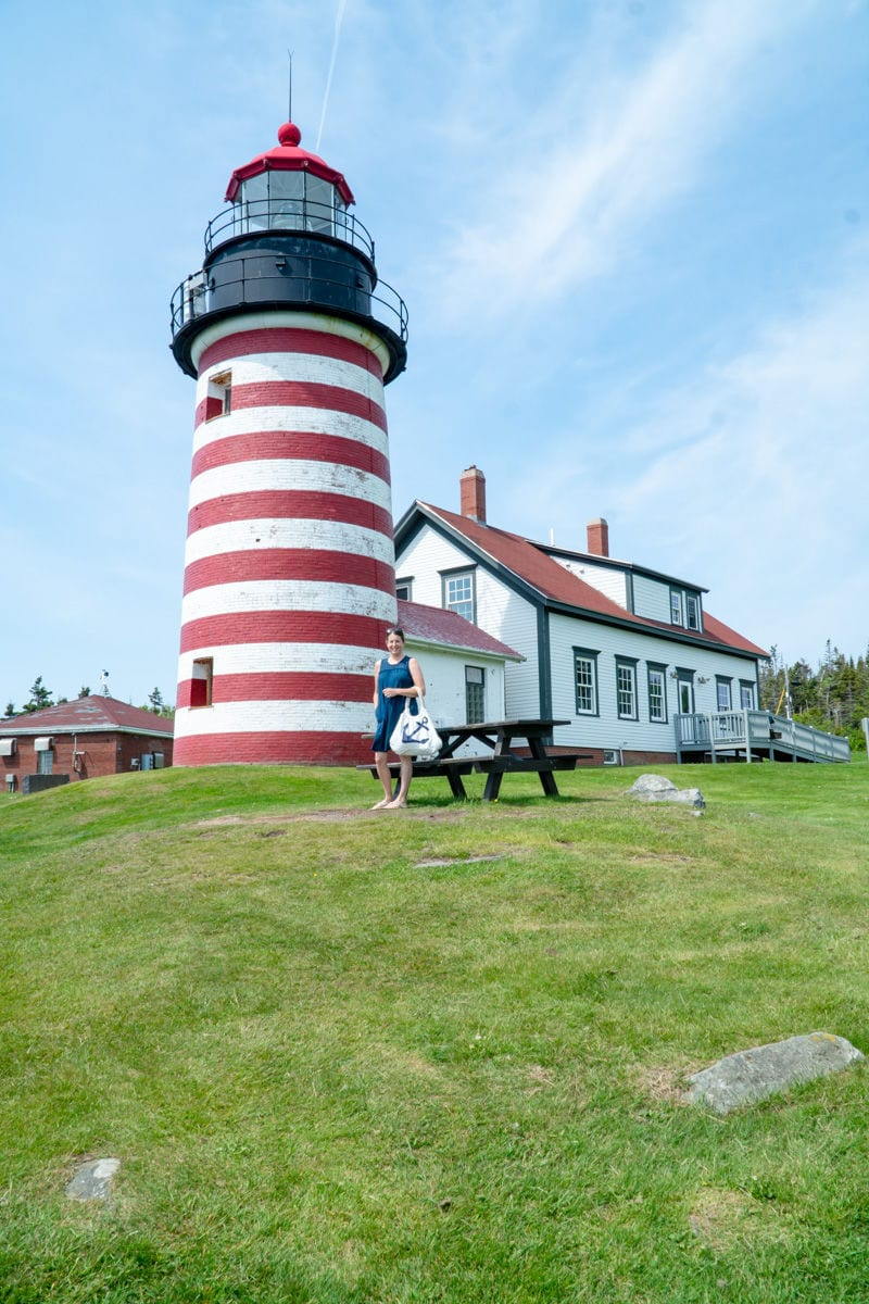 Woman on blue dress holding tote bag with a blue anchor standing in front of red and white striped West Quoddy Head Lighthouse