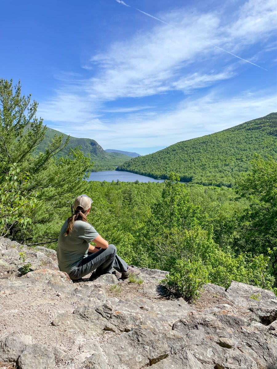woman sitting on rock overlooking pond and valley