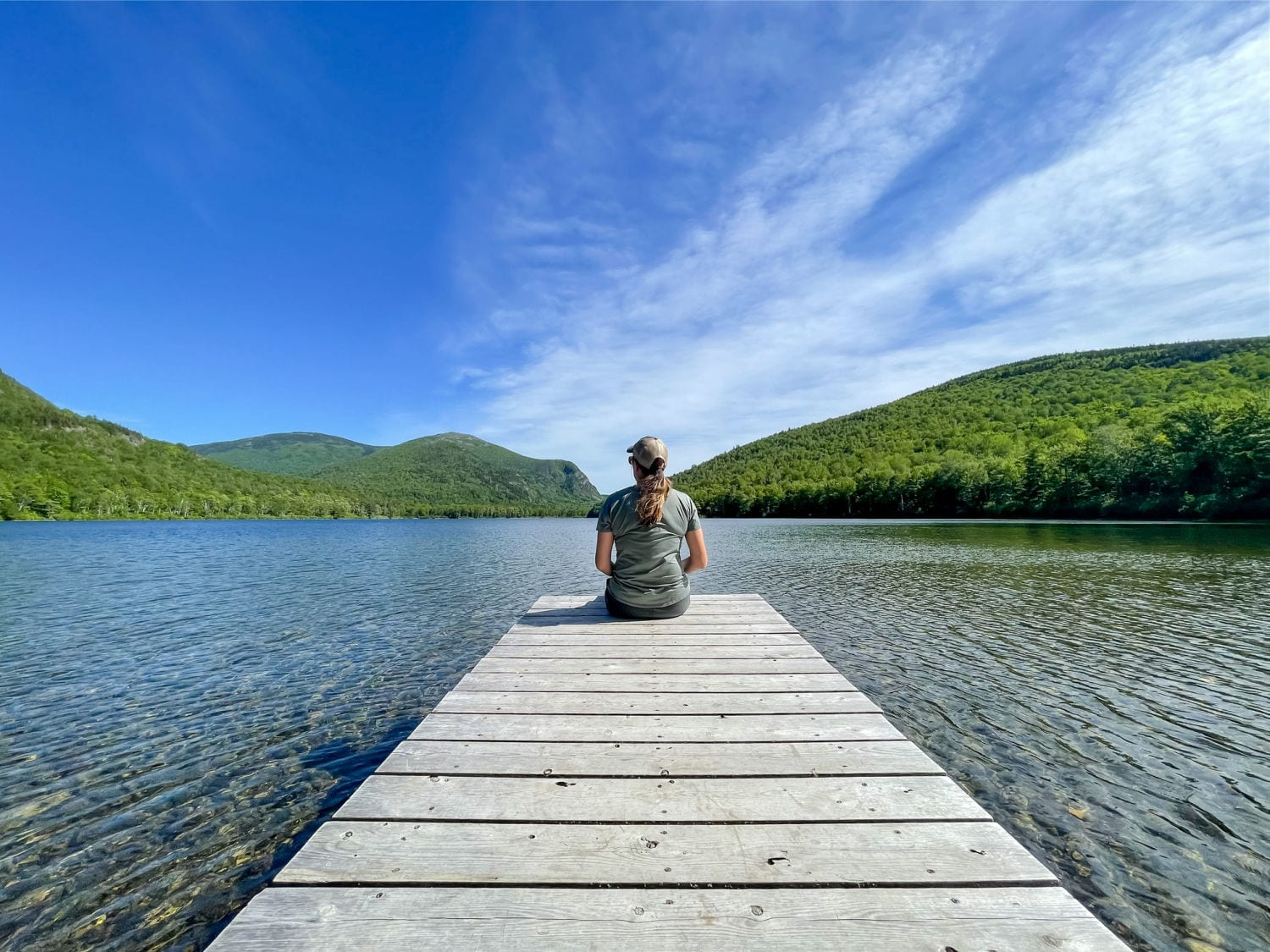 woman sitting on dock looking out on South Branch Pond in Baxter State Park