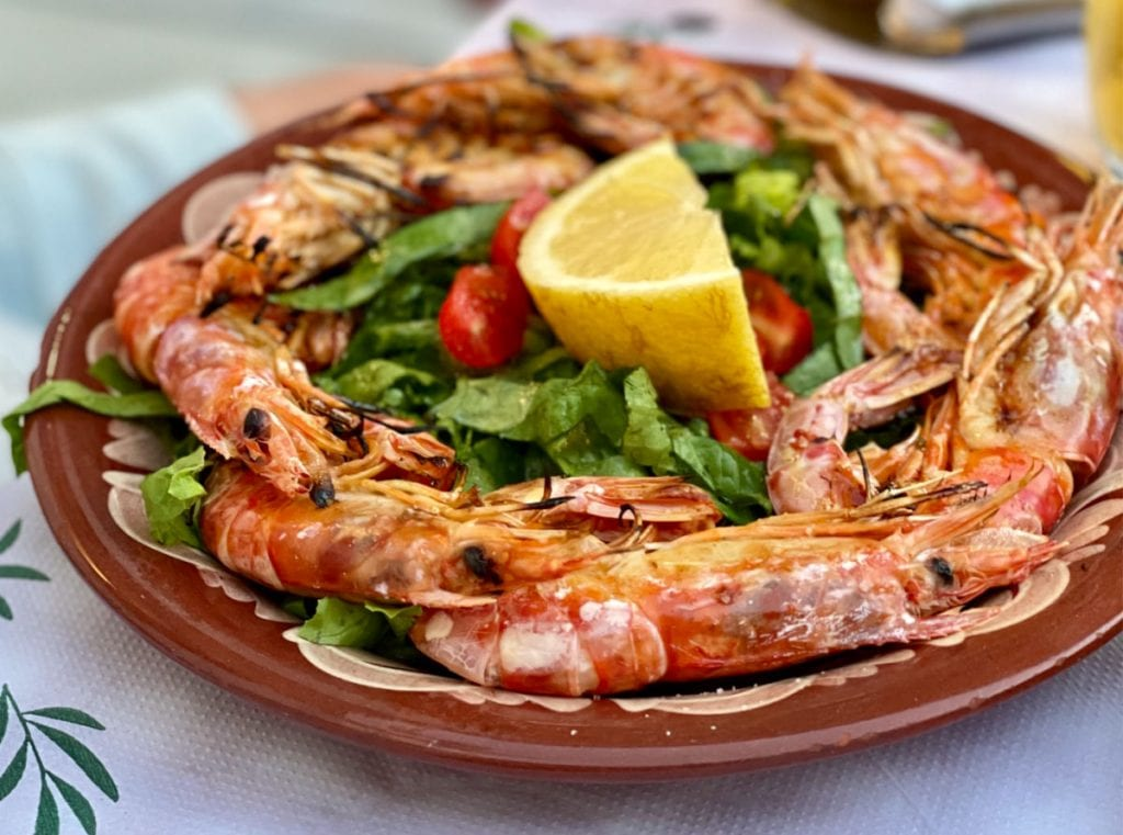 Large prawns on a brown plate with a lemon wedge and salad