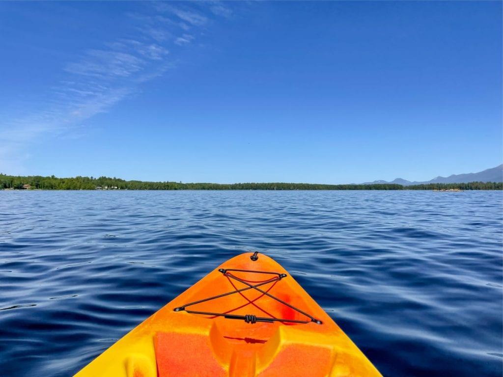 front tip of orange kayak on lake