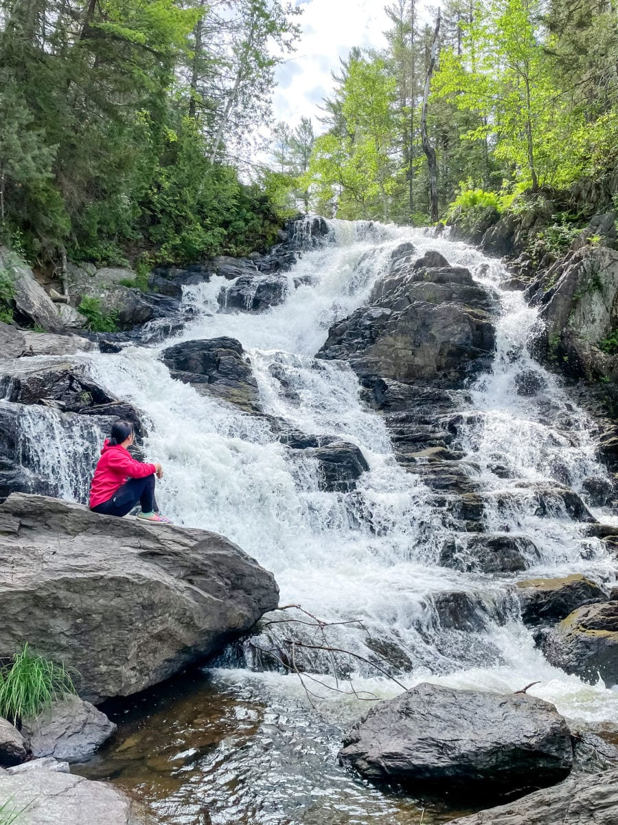 woman in red jacket and black pants sitting on rocks looking at Shin Brook Falls