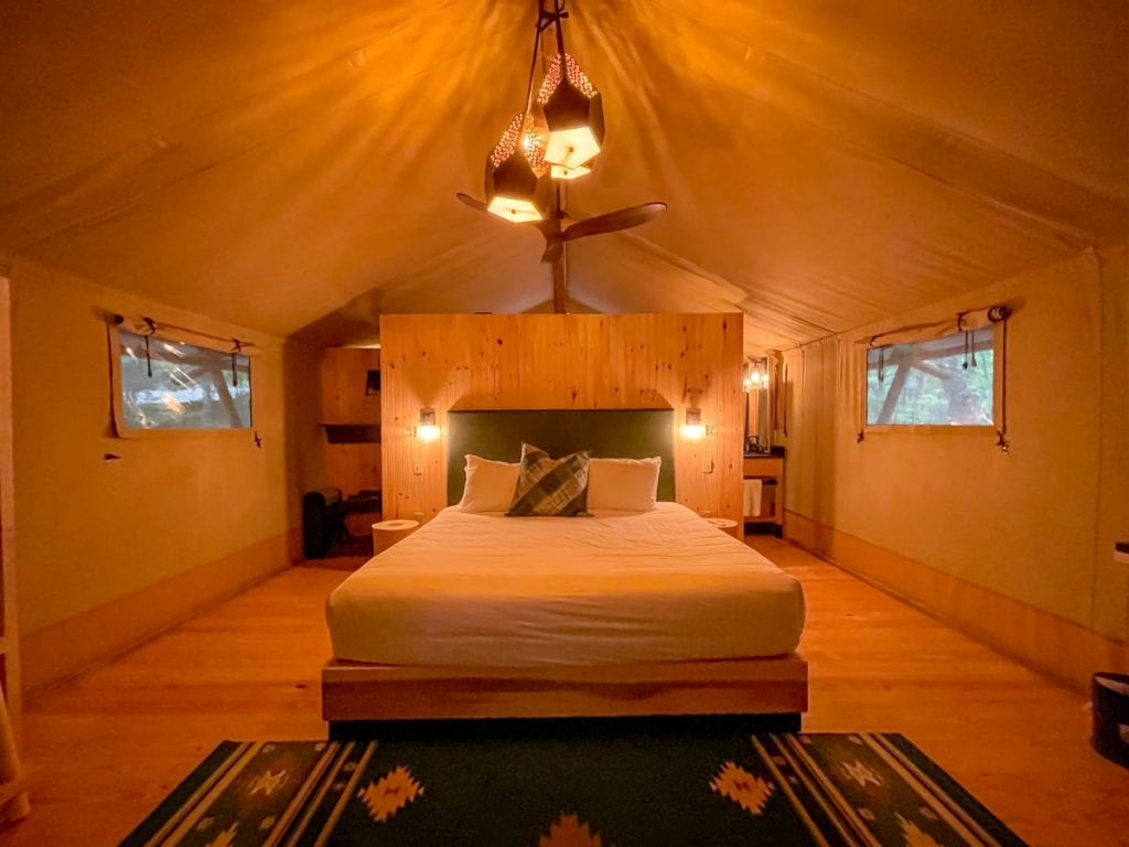 Inside the Bayberry tent at Terramor in the evening with the ceiling fan light on looking at the bed