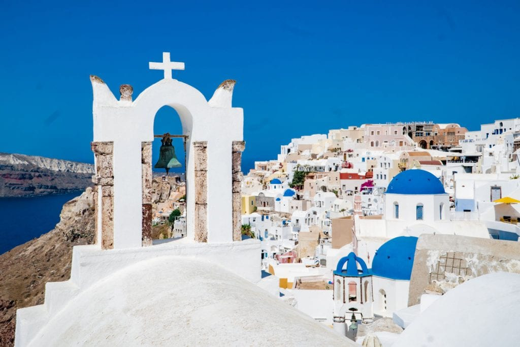 Oia town on cliff with church bell and blue dome in the foreground