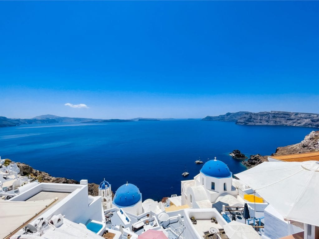 Caldera view with two blue domed churches in Oia Santorini
