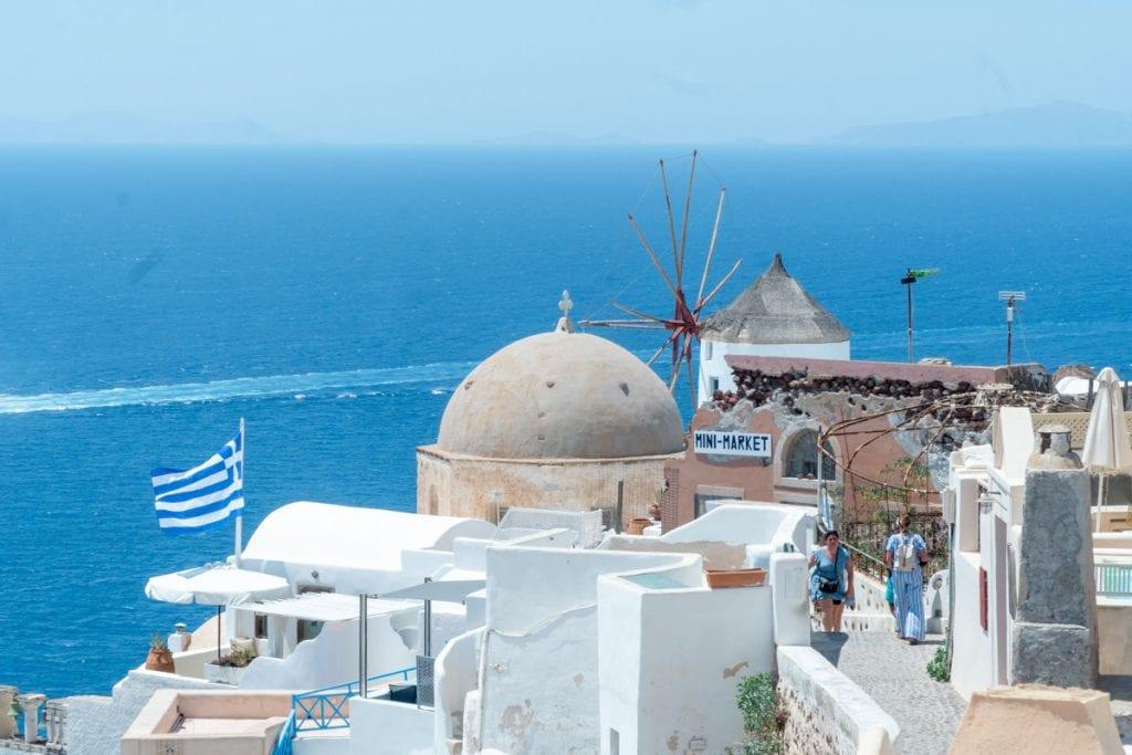 Windmill, domed church and Greece flag in Oil Santorini