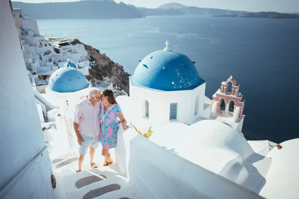 Couple kissing in front of two blue domed churches in Oia Santorini