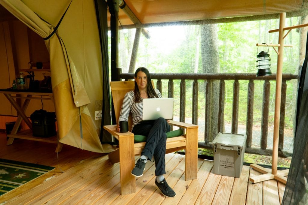 Woman sitting on porch of Bayberry tent with computer