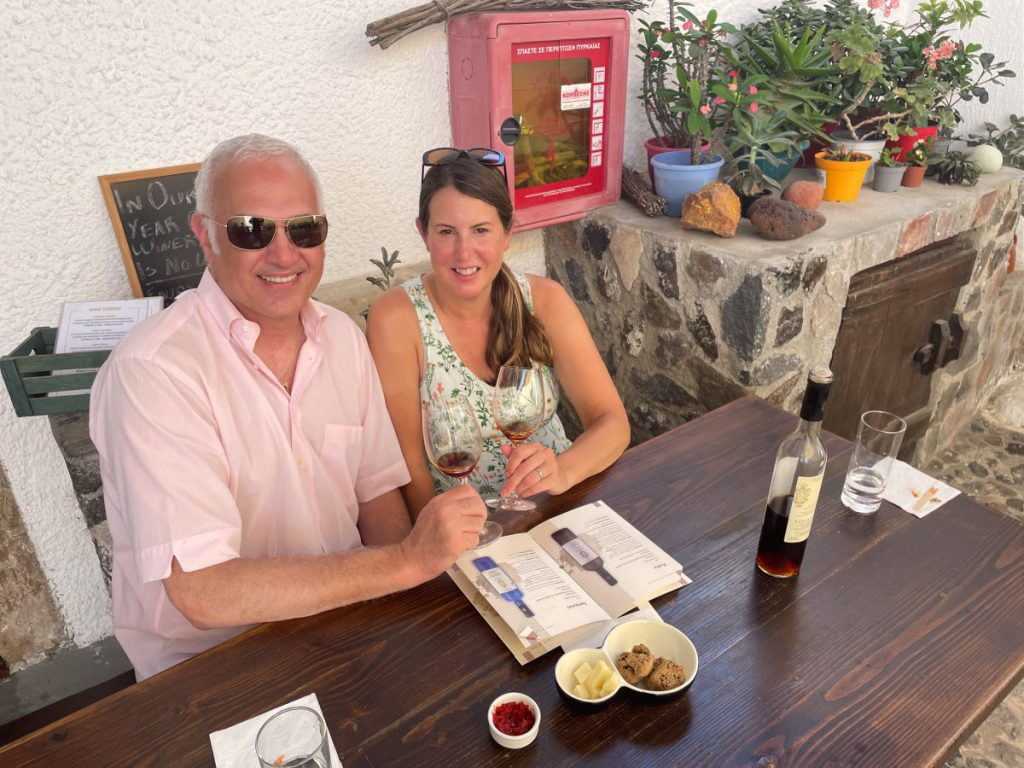 Couple holding wine glasses at wine tasting in Gavalas winery