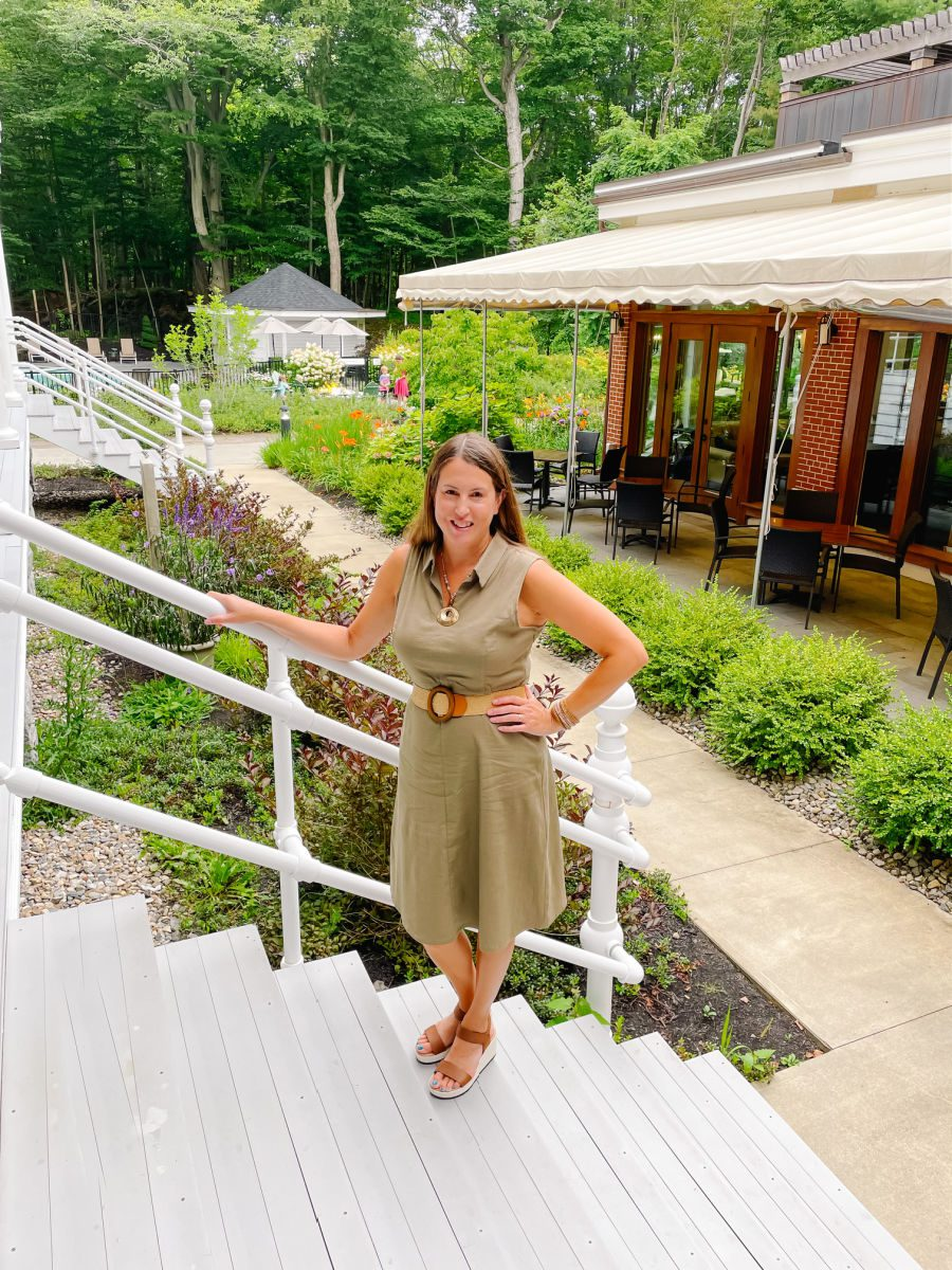 Woman in brown dress standing on stairs in courtyard at the Inn at Diamond Cove
