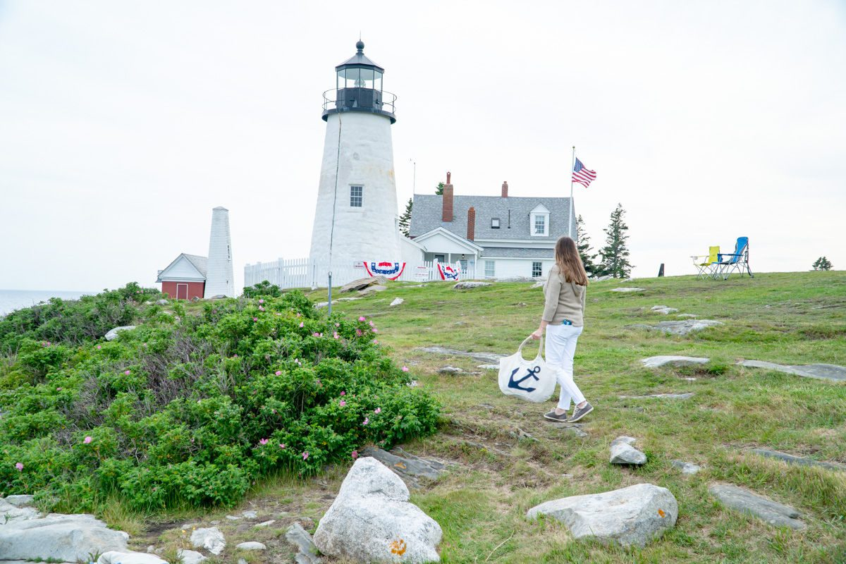 Woman holding anchor Maine Sea Bag in front of Pemaquid Point Lighthouse