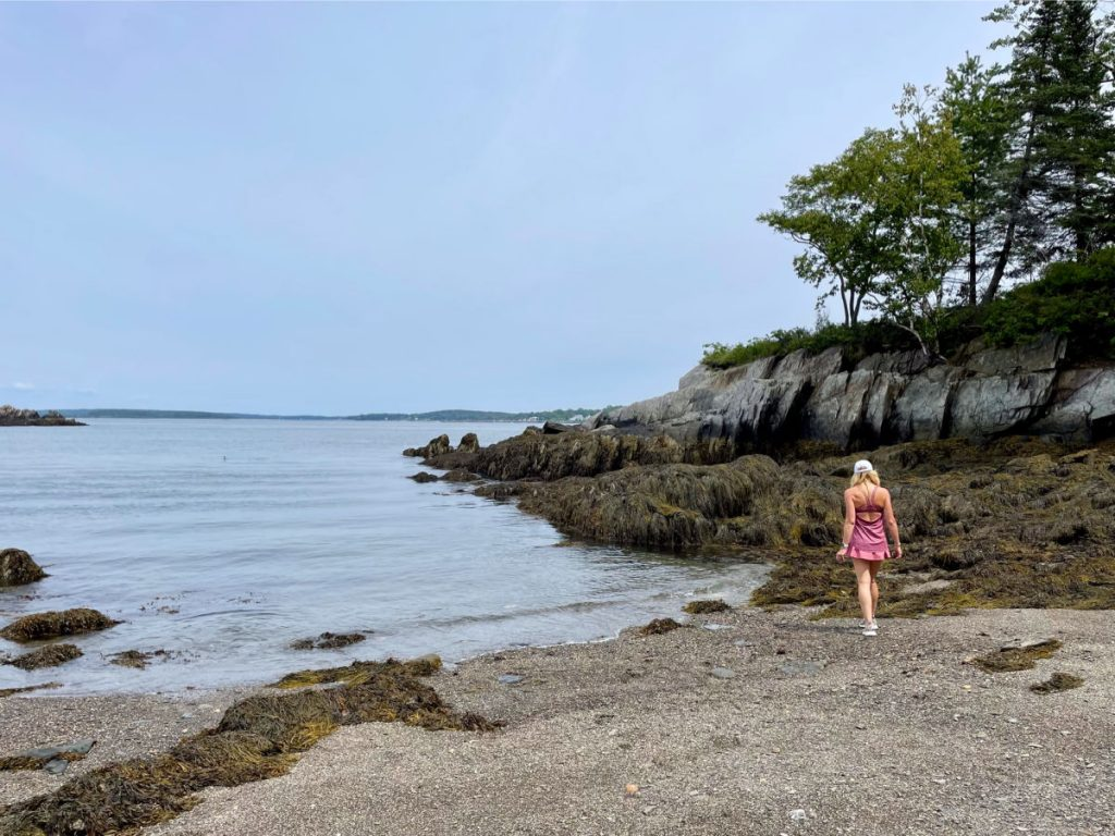 Woman in pink walking on rocky beach