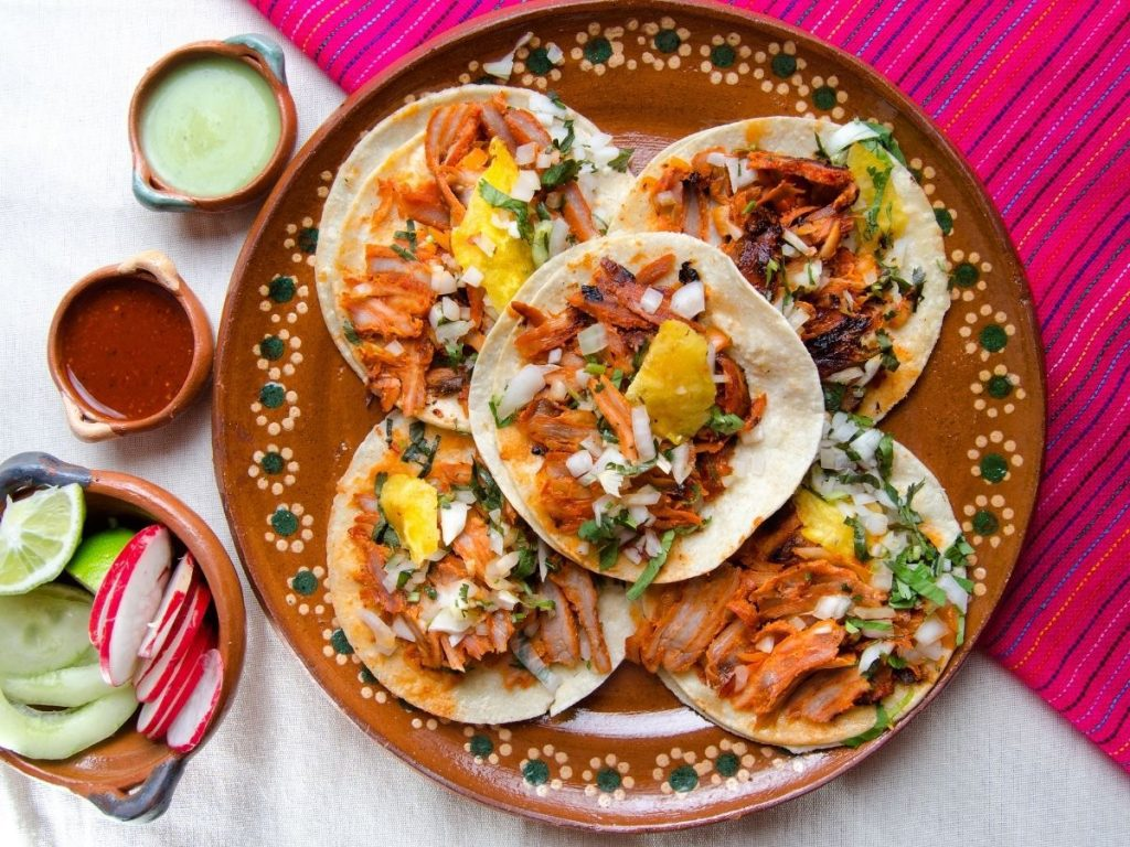 Tacos on a platter and a pink striped tablecloth with sauces on the side (Canva)