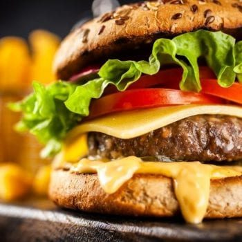 Cheeseburger with fries in the background