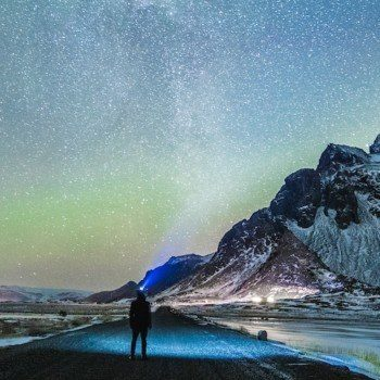 Man standing in road looking up at northern lights with snow covered mountains in the distance