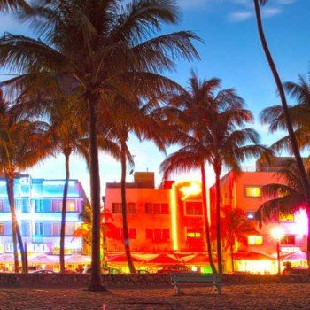 Buildings lit up at night along Ocean Drive in Miami at sunset