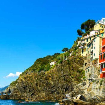 Riomaggiore village panoramic view on cliff rocks, boats and sea., Seascape in Five lands, Cinque Terre National Park, Liguria Italy Europe.