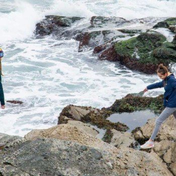 woman and teen girl jumping on rocks at Beavertail State park