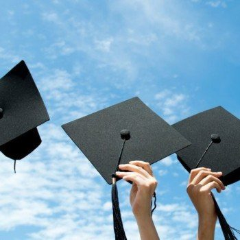 Graduation hats held in the air against a blue sky