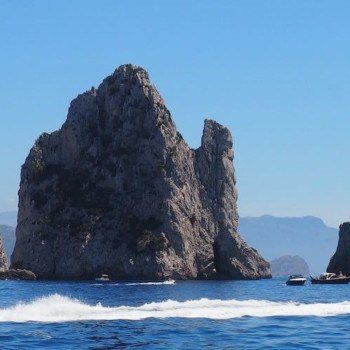 Faraglioni rocks off of Capri Italy with boat in water crossing in front