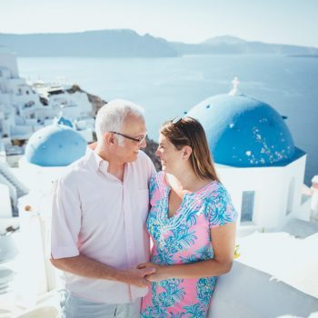 Couple in Oia Santorini with blue dome church in background
